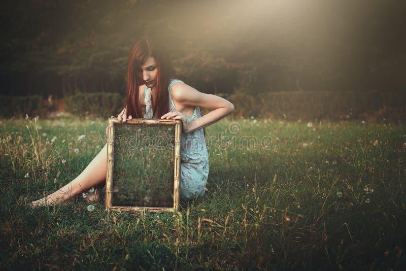 Donna con lo specchio sconosciuto su un prato immagine stock libera da diritti