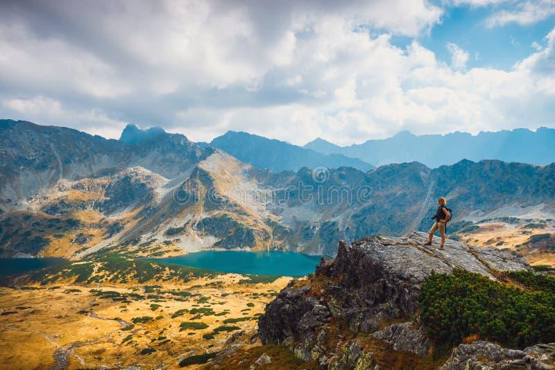 Donna con lo zaino che sta sopra una montagna immagine stock libera da diritti