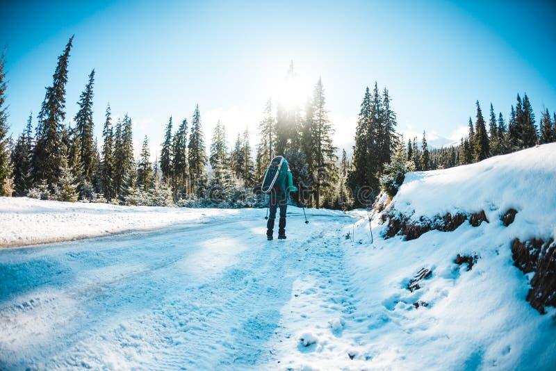 Donna con lo zaino e le racchette da neve nelle montagne di inverno fotografia stock