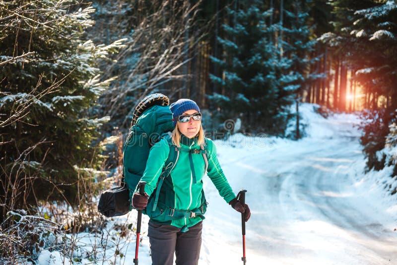 Donna con lo zaino e le racchette da neve nelle montagne di inverno fotografia stock libera da diritti