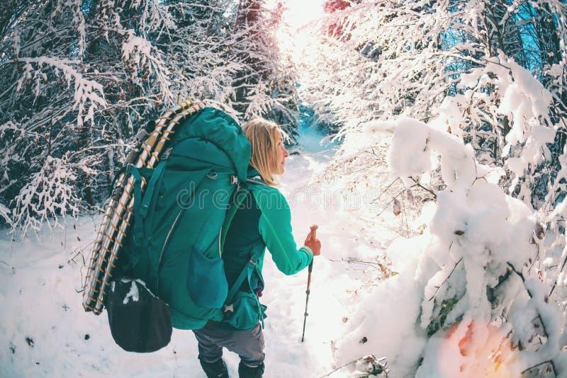 Donna con lo zaino e le racchette da neve nelle montagne di inverno immagini stock