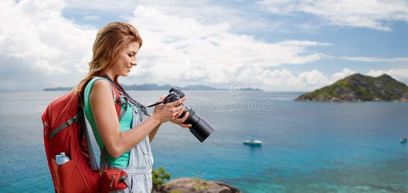 Donna con lo zaino e macchina fotografica sopra la spiaggia immagine stock