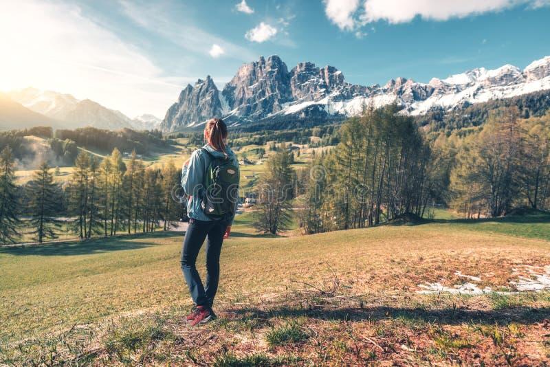 Donna con lo zaino in valle della montagna al tramonto in primavera fotografia stock libera da diritti