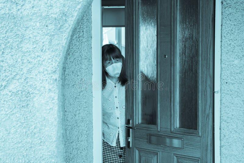 Donna con maschera protettiva che guarda fuori da dietro una porta parzialmente aperta epidemia di coronavirus nel Regno Unito immagini stock libere da diritti