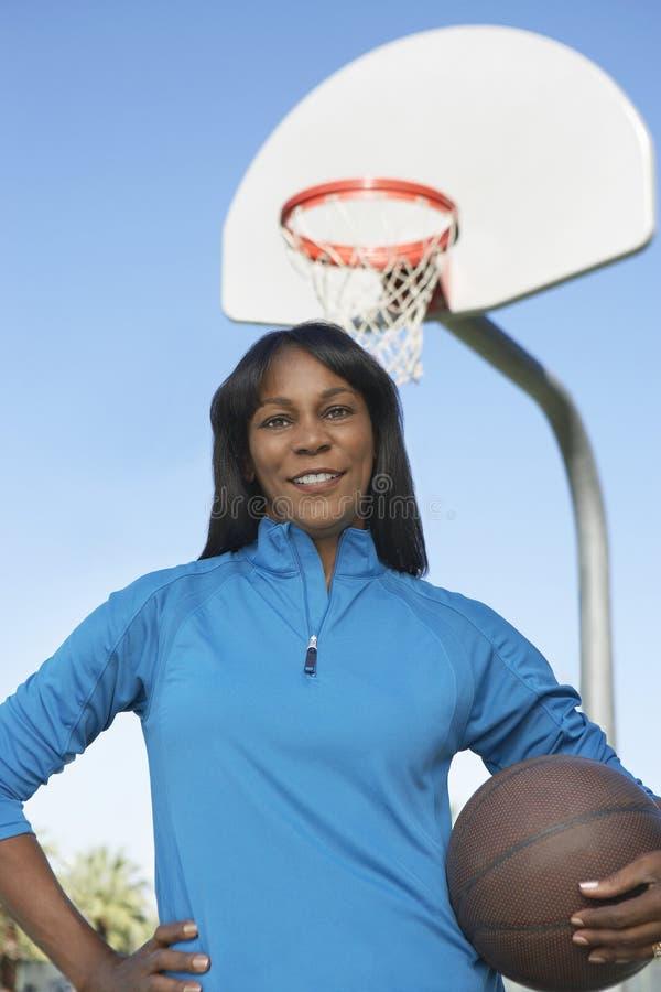 Donna con pallacanestro alla corte fotografie stock