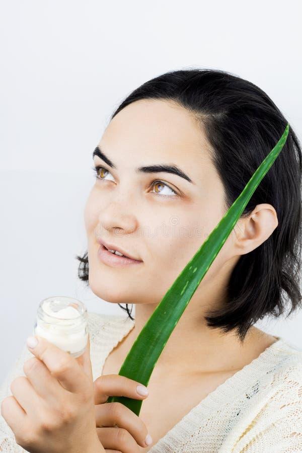 Donna con pelle e capelli sani con la latta crema fotografia stock libera da diritti