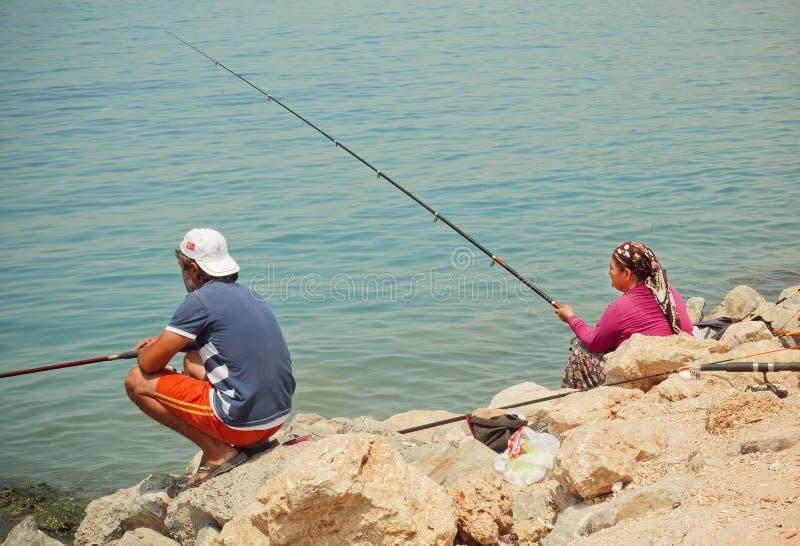 Donna con pesca dell'uomo e della barretta su una baia con acqua blu del mar Egeo fotografia stock libera da diritti