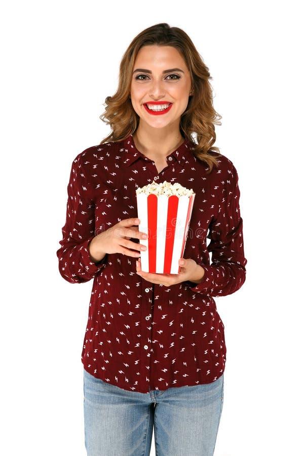 Donna con popcorn in sue mani che posano sul fondo bianco fotografia stock libera da diritti