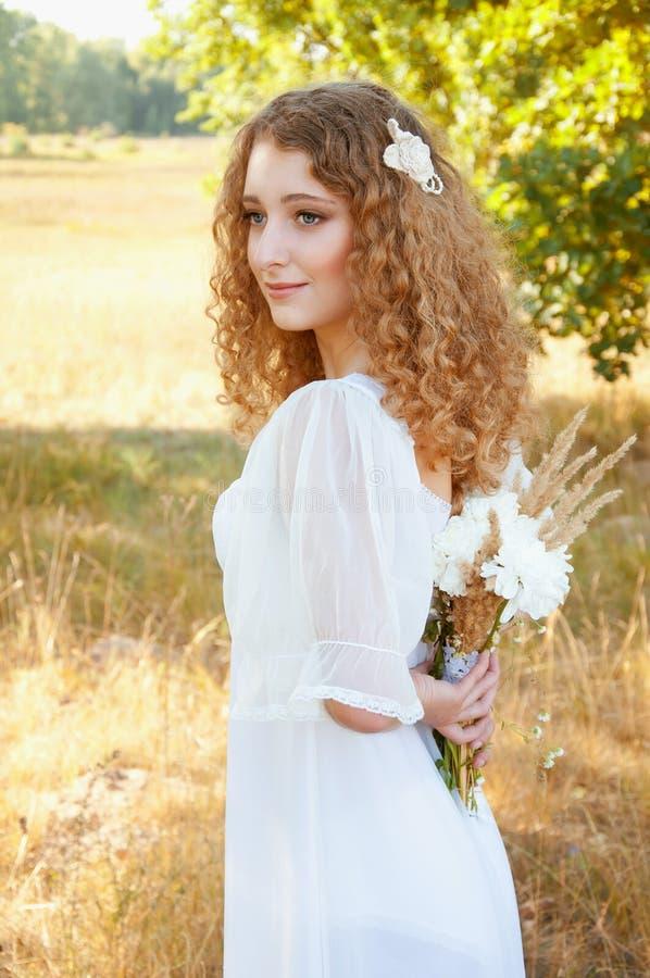 Donna con stare sorridente dei capelli dorati ricci nel campo fotografia stock