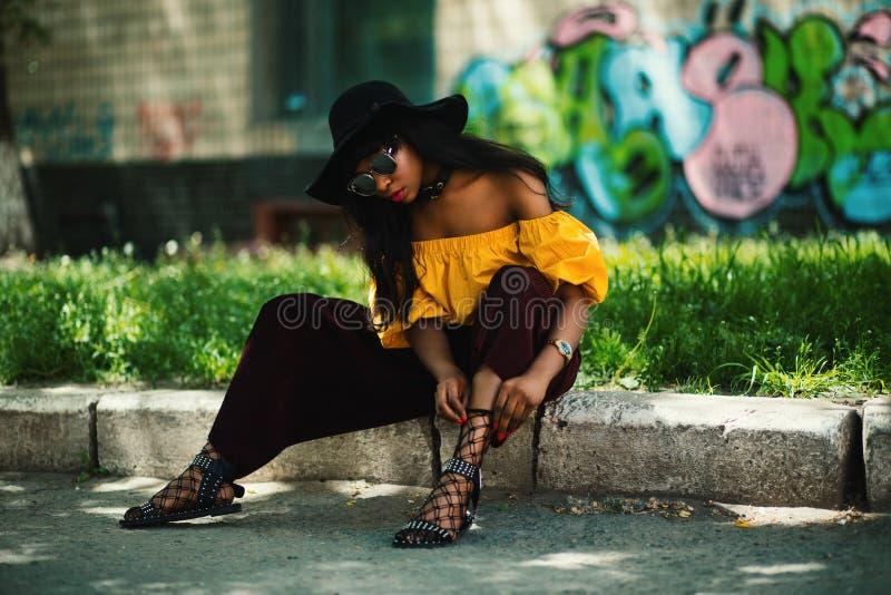 Donna con top giallo off-shoulder e pantaloncini neri seduta su sandali per pizzi per sidewalk fotografia stock libera da diritti