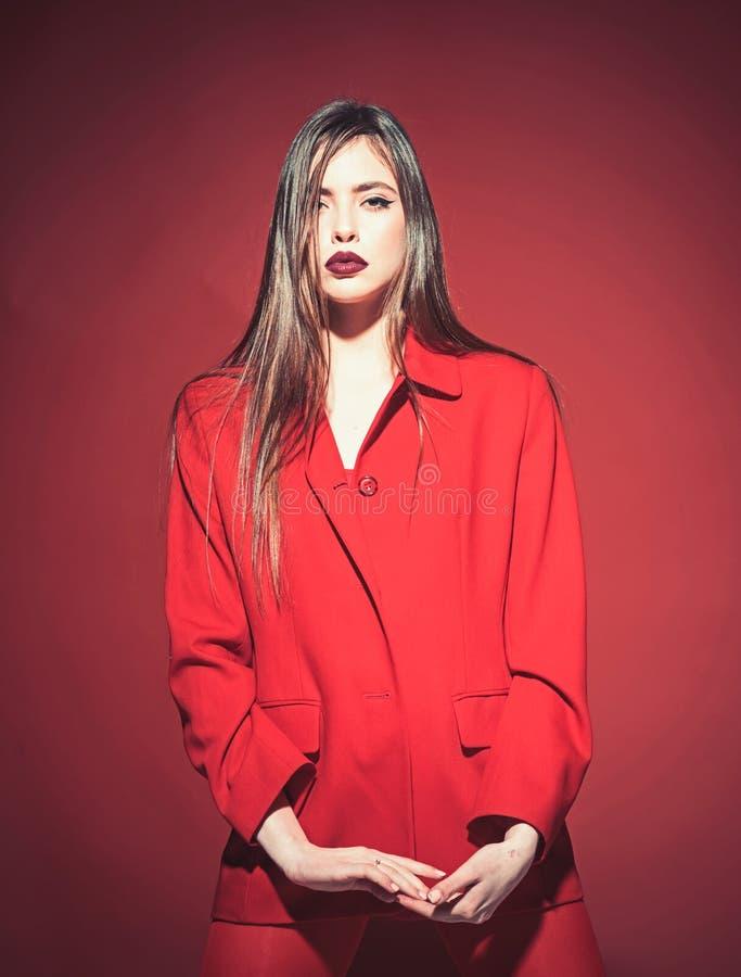 Donna con trucco alla moda e capelli lunghi che posano in attrezzatura rossa totale Concetto di modo Signora con le labbra scure  fotografia stock libera da diritti