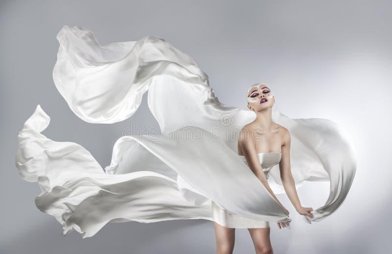 Donna con trucco creativo luminoso in un volo bianco del panno fotografie stock libere da diritti