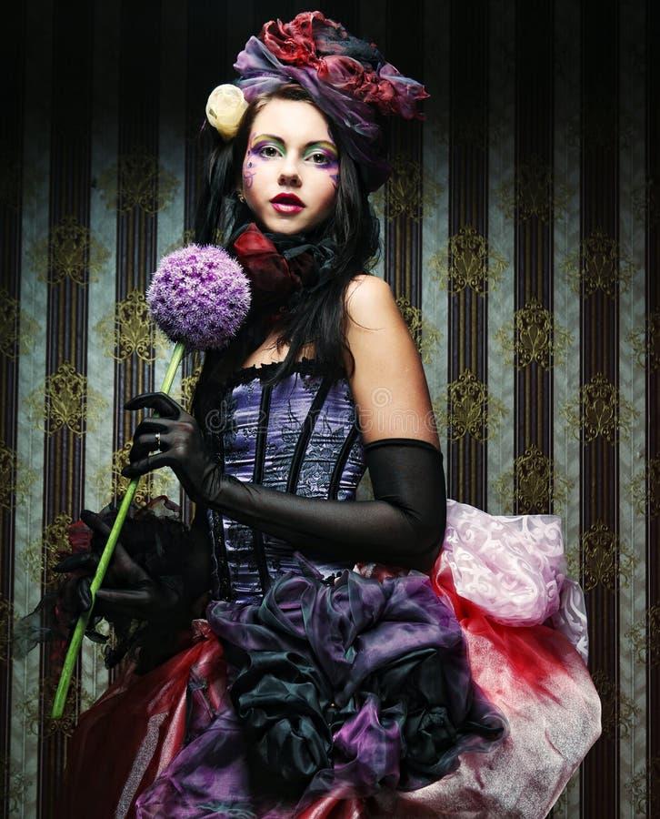 Donna con trucco creativo nello stile della bambola con il fiore fotografia stock