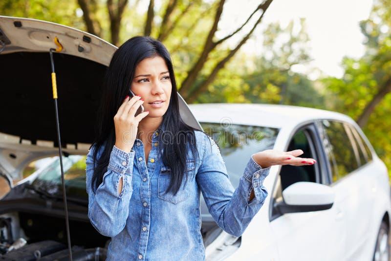 Donna con un'automobile rotta che richiede l'assistenza fotografie stock libere da diritti