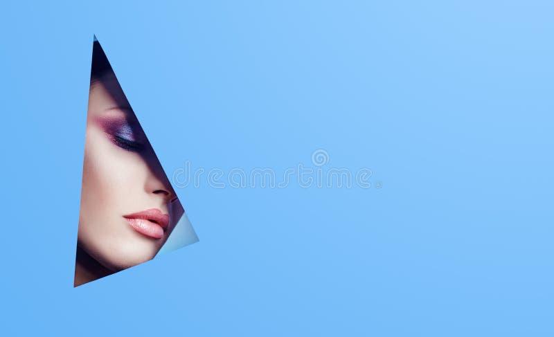 Donna con un bello sguardo attraverso un foro triangolare nella carta blu, nel trucco luminoso e nel rossetto rosa Cosmetici di p fotografia stock