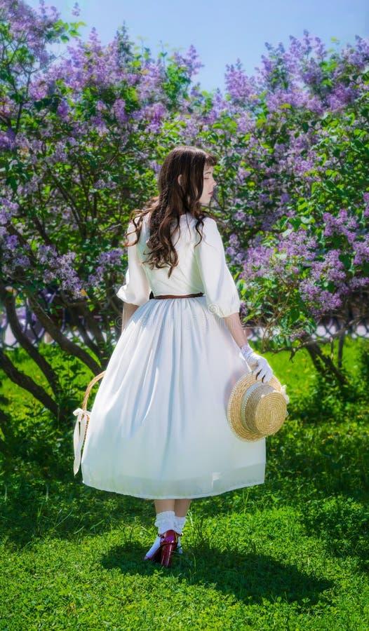 Donna con un canestro in sue mani in una passeggiata in giardino immagini stock