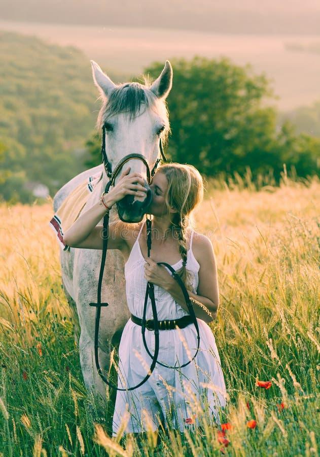 Donna con un cavallo in un prato immagine stock