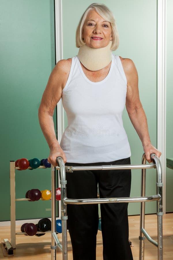 Donna con un collo ortopedico facendo uso del camminatore immagine stock