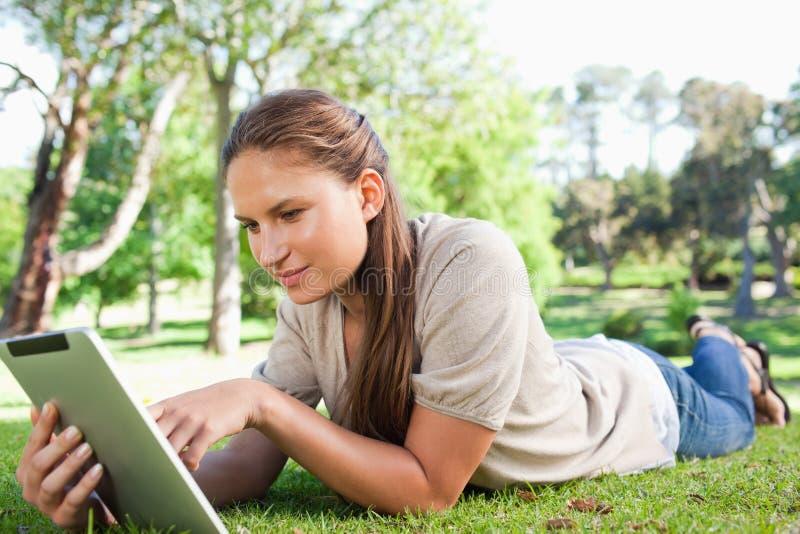 Donna con un computer della compressa che si trova sul prato inglese immagini stock