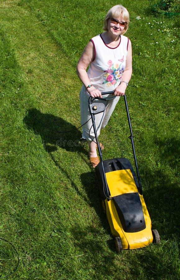 Donna con un falciatore elettrico al cottage fotografia stock libera da diritti