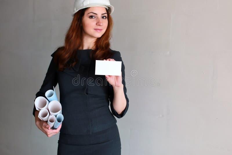 Donna con un foglio bianco di carta in sua mano sul si della costruzione fotografie stock libere da diritti