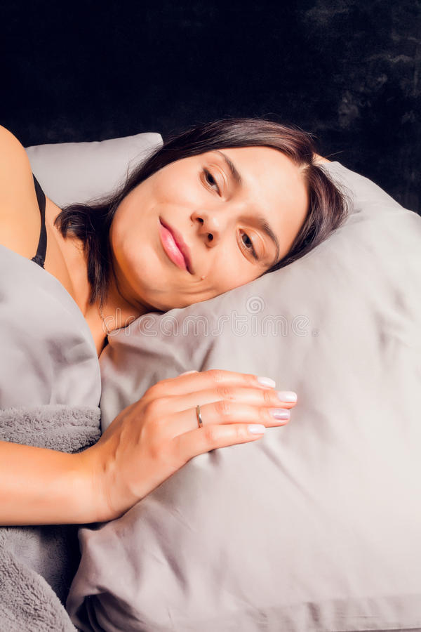 Donna con un fronte di sorriso che si trova a letto sul fondo scuro fotografia stock immagine - Letto che si chiude ...