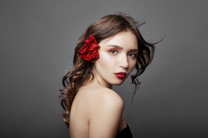 Donna con un grande fiore rosso in suoi capelli Ragazza castana con un fiore rosso che posa su un fondo grigio Grandi bei occhi fotografie stock