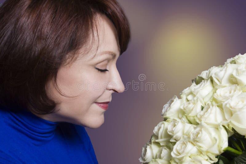 Donna con un mazzo delle rose fotografia stock libera da diritti