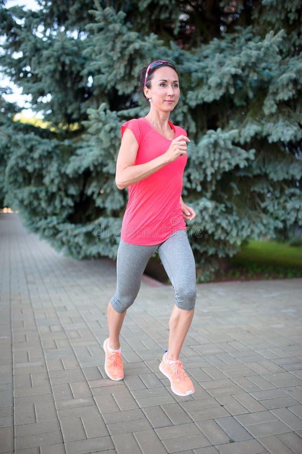 Donna con un paio atletico delle gambe che vanno per un trotto L sana fotografia stock libera da diritti