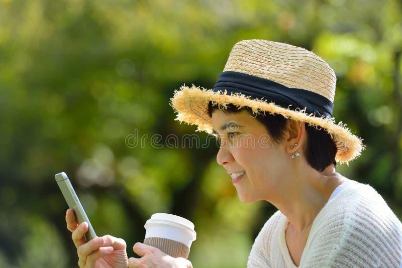 Donna con un telefono cellulare nel parco immagine stock libera da diritti