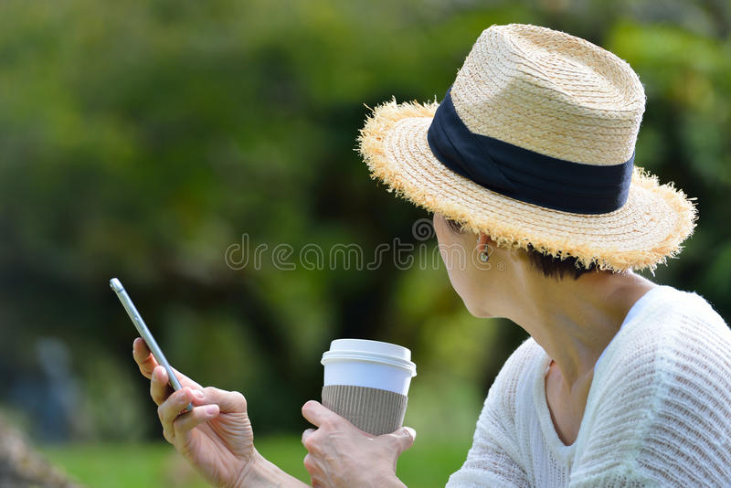 Donna con un telefono cellulare nel parco fotografie stock libere da diritti