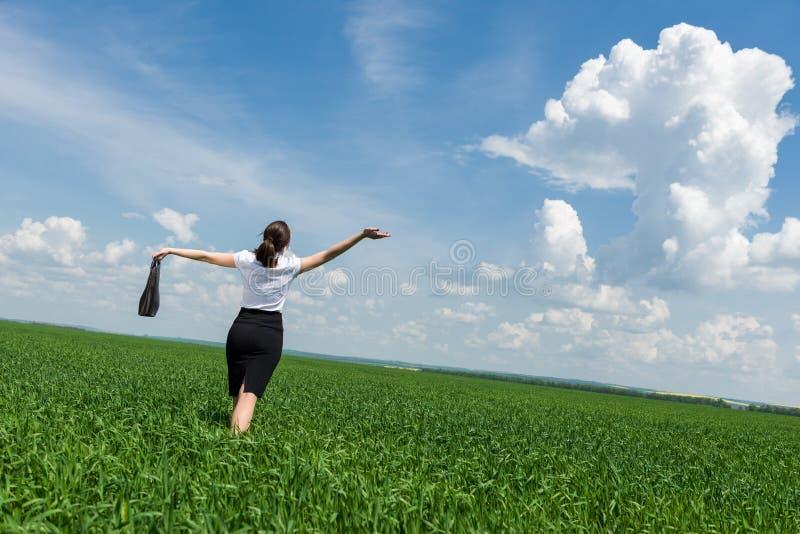 Donna con una cartella che cammina sull'erba fotografia stock libera da diritti