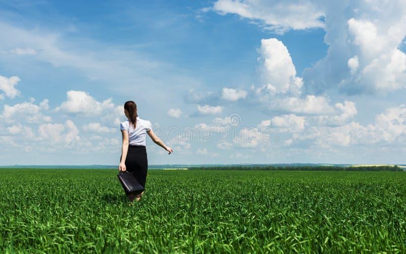 Donna con una cartella che cammina sull'erba immagine stock