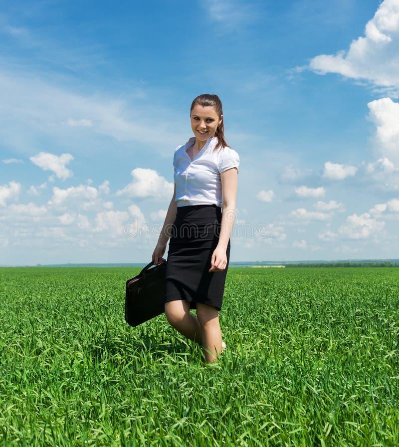 Donna con una cartella che cammina sull'erba fotografia stock