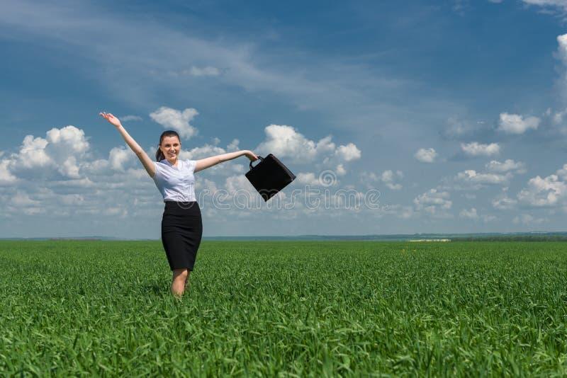 Donna con una cartella che cammina sull'erba fotografie stock libere da diritti