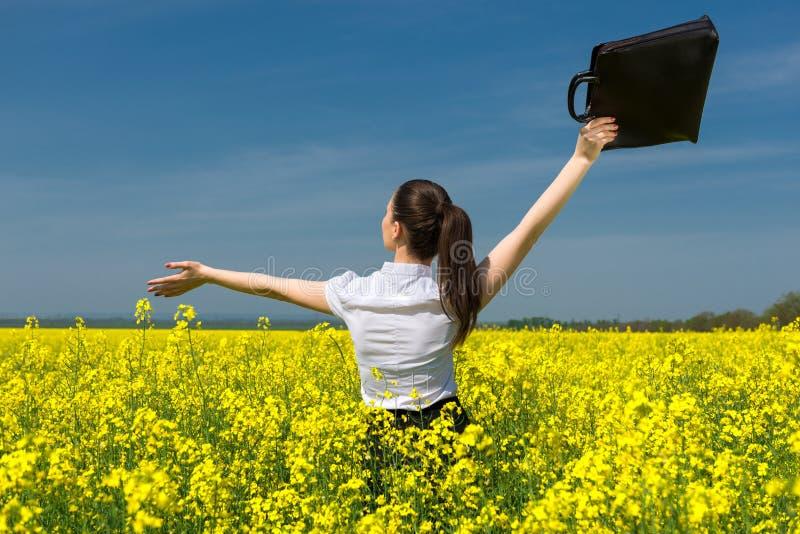 Donna con una cartella sul giacimento di fiore giallo fotografie stock