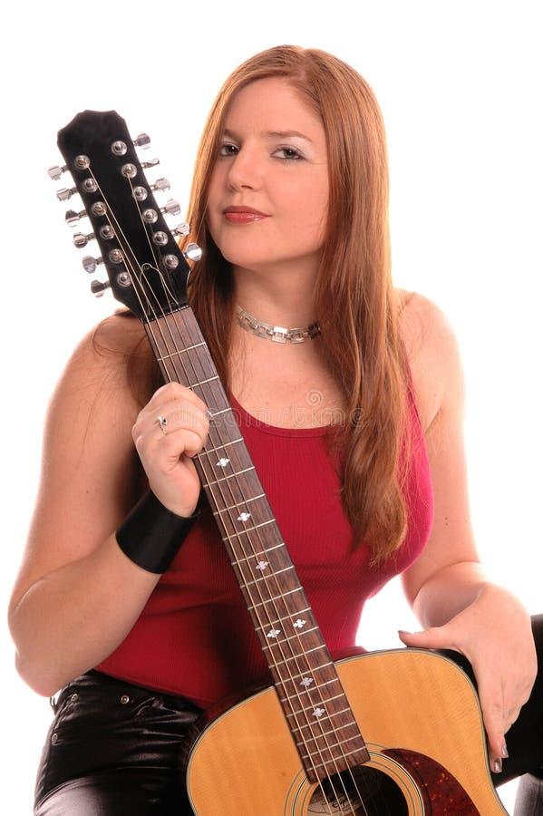 Donna con una chitarra acustica fotografia stock libera da diritti