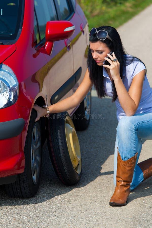 Donna con una gomma piana in automobile immagini stock