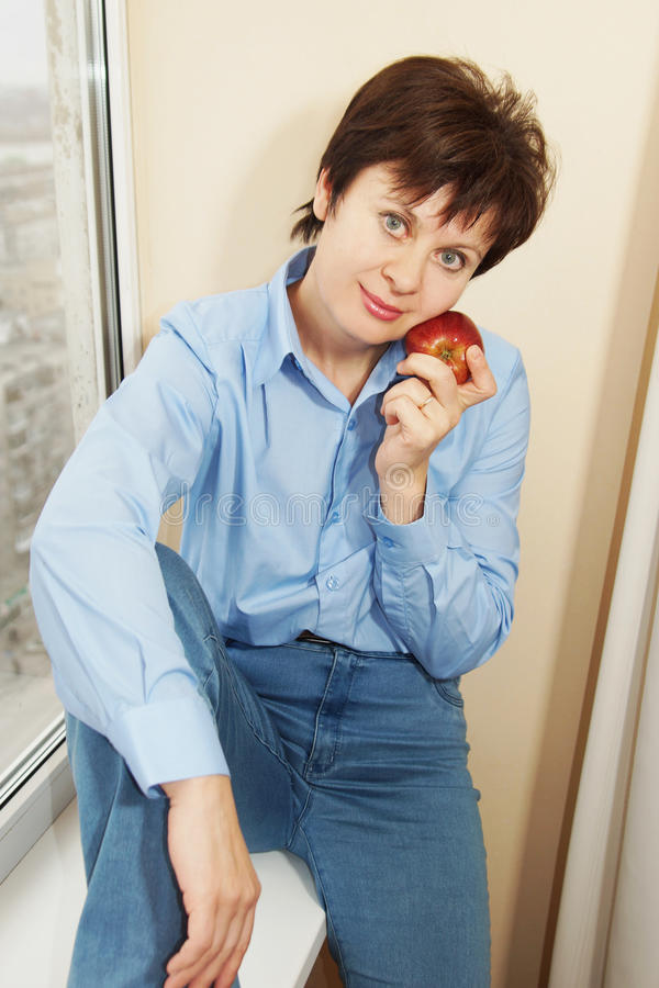 Donna con una mela rossa che si siede al davanzale fotografia stock