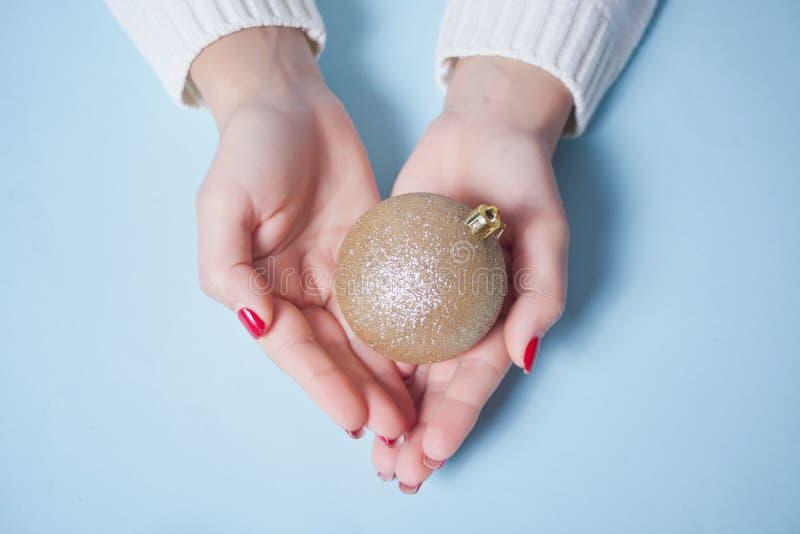 Donna con una palla di Natale dorata in mano sullo sfondo blu immagini stock