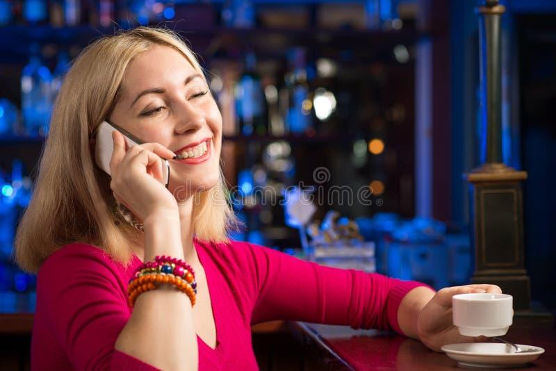 Donna con una tazza di caffè e un telefono cellulare immagini stock libere da diritti