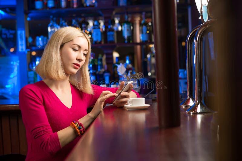 Donna con una tazza di caffè e un telefono cellulare fotografia stock libera da diritti