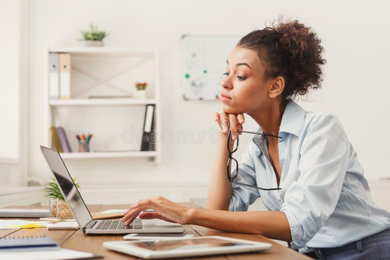 Donna concentrata di affari che lavora al computer portatile all'ufficio fotografie stock