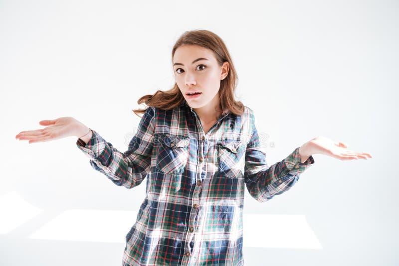 Donna confusa che scrolla le spalle le spalle e che tiene copyspace su entrambe le palme immagini stock