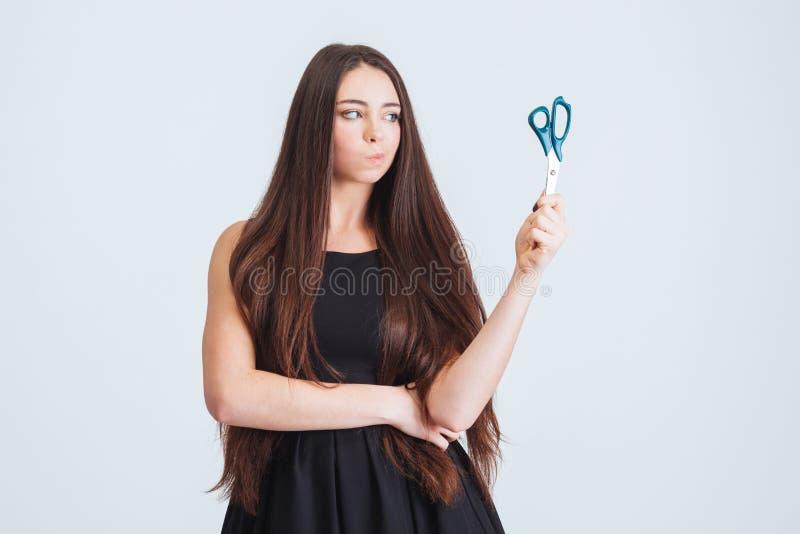 Donna confusa infelice con le forbici lunghe di condizione e della tenuta dei capelli fotografia stock libera da diritti