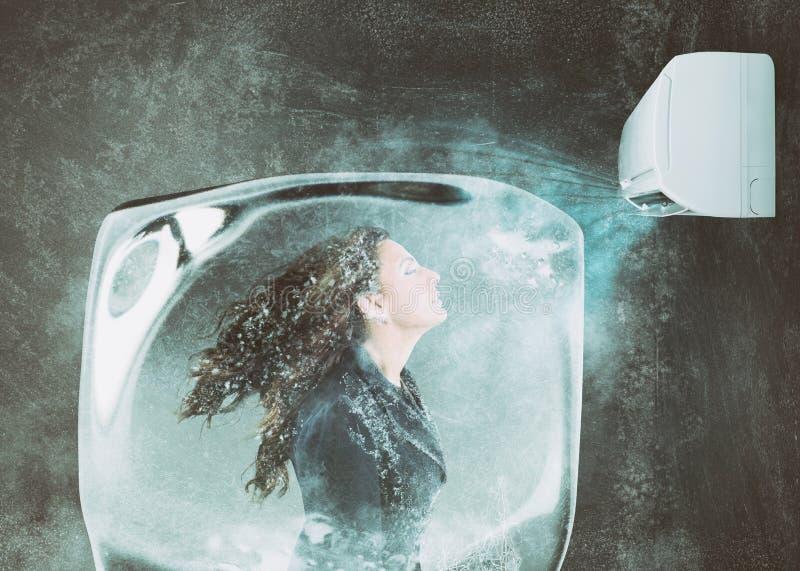 Donna congelata in un cubetto di ghiaccio sotto il getto d'aria di condizionatore d'aria fotografie stock