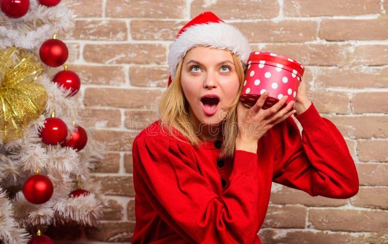 Donna in contenitore di regalo della tenuta del cappello di Santa La ragazza celebra vicino all'albero di Natale Disimballaggio d fotografia stock libera da diritti
