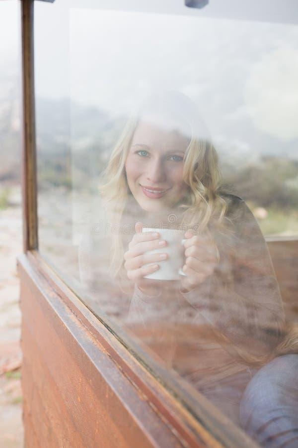 Donna contenta con la tazza di caffè che guarda fuori attraverso la finestra fotografie stock libere da diritti