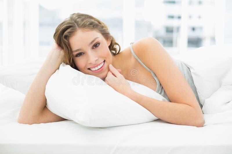 Donna contenta pacifica che si trova nel suo letto nell'ambito della copertura fotografia stock
