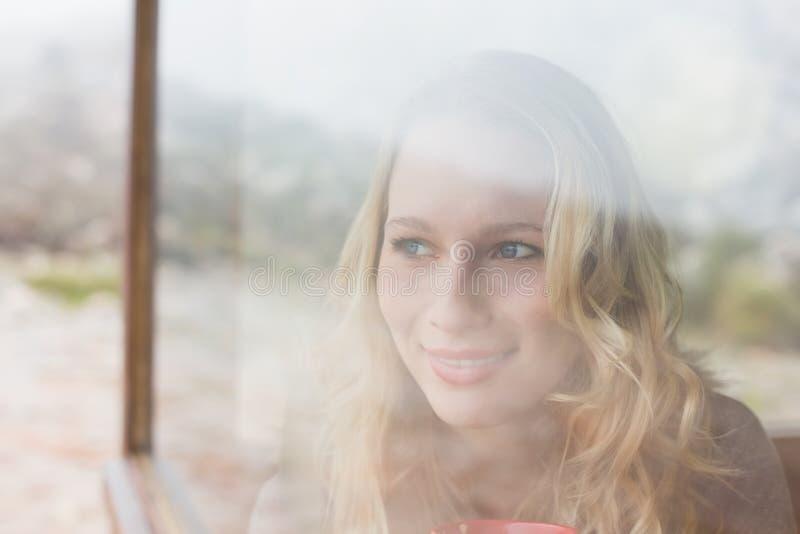 Donna contenta premurosa che guarda fuori attraverso la finestra immagine stock libera da diritti